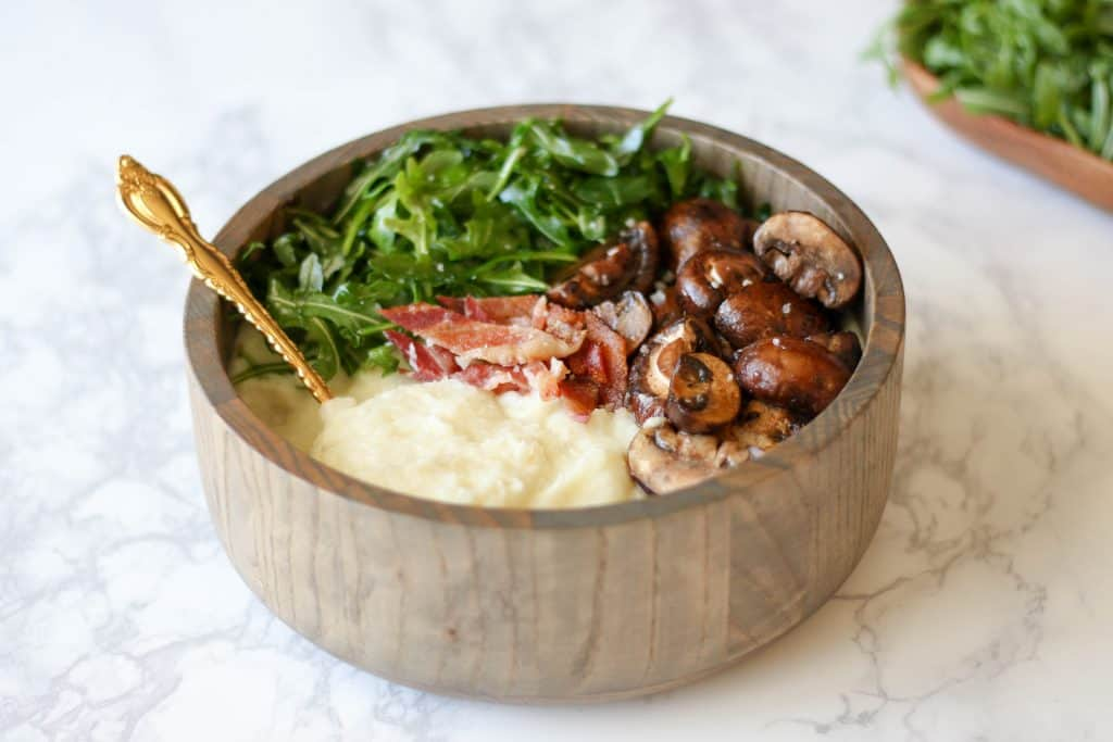 A wooden bowl full of mashed cauliflower, bacon, arugula, and sauteed mushrooms on a marble table.