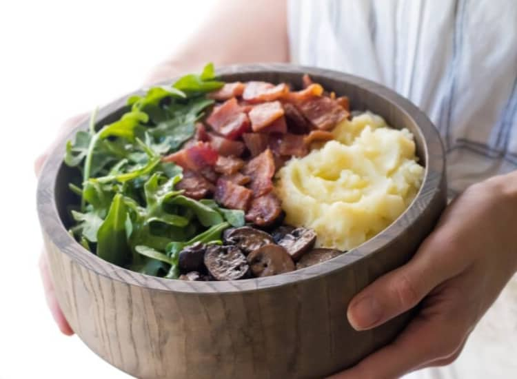 Hands holding a wooden bowl holding an AIP breakfast of mashed cauliflower, sauteed mushrooms, bacon, and arugula.