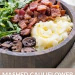 wooden bowl holding an a Whole30 breakfast of mashed cauliflower, sauteed mushrooms, bacon, and arugula. Pink label at the bottom with white text reads: Mashed Cauliflower Breakfast Bowl, Whole30, Paleo, AIP.