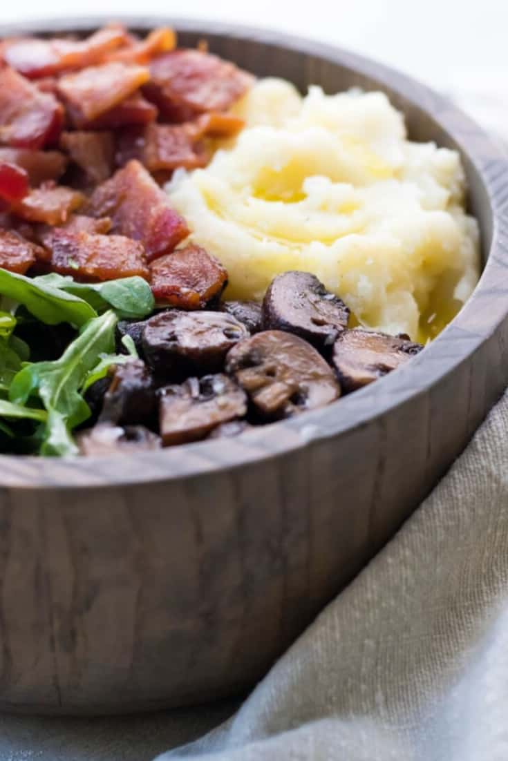 wooden bowl holding an a Whole30 breakfast of mashed cauliflower, sauteed mushrooms, bacon, and arugula.