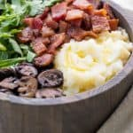 wooden bowl holding an AIP breakfast of mashed cauliflower, sauteed mushrooms, bacon, and arugula.