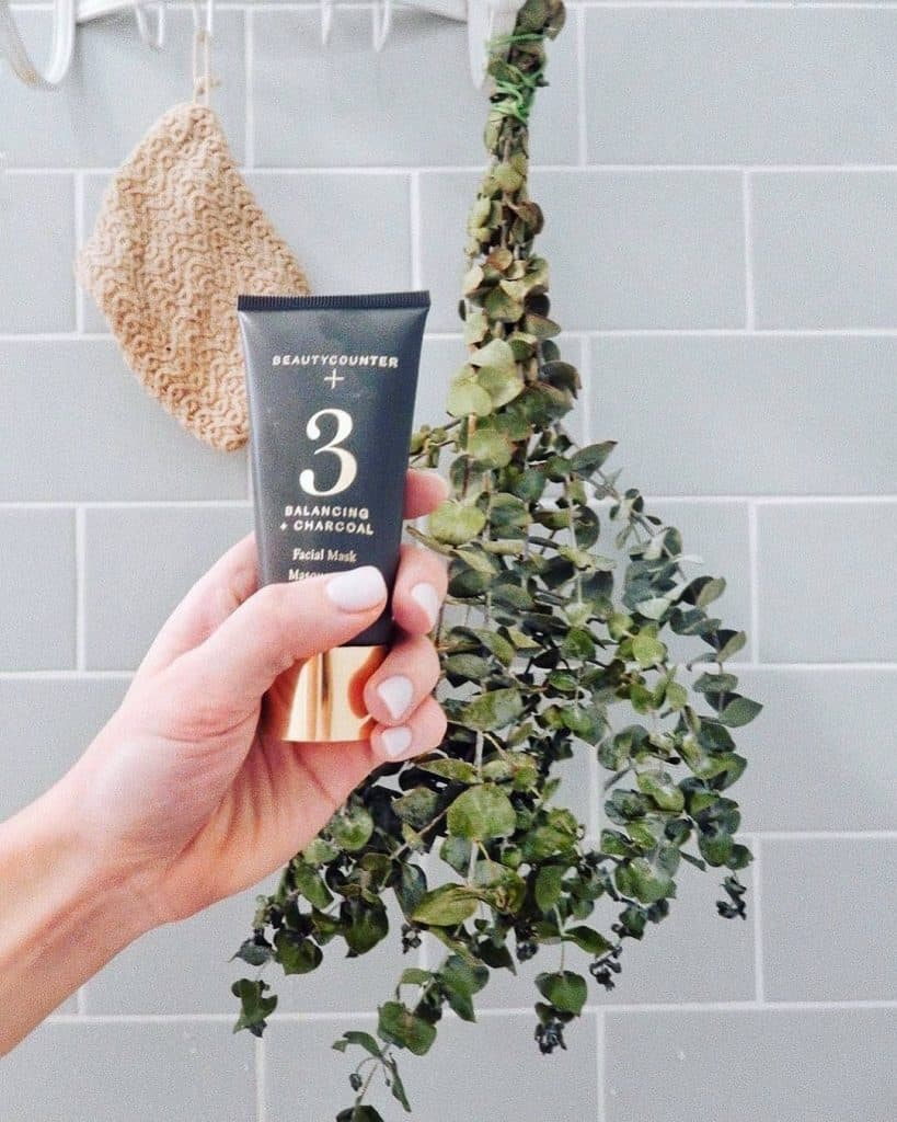 A photo of a shower with grey tile, a bunch of eucalyptus hanging on the shower head and a hand holding a tube of Beautycounter No. 3 Balancing + Charcoal Facial Mask.