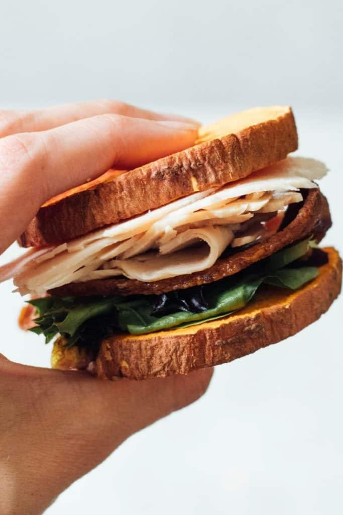 A hand holds a turkey sandwich with bacon and lettuce on a sweet potato bun.