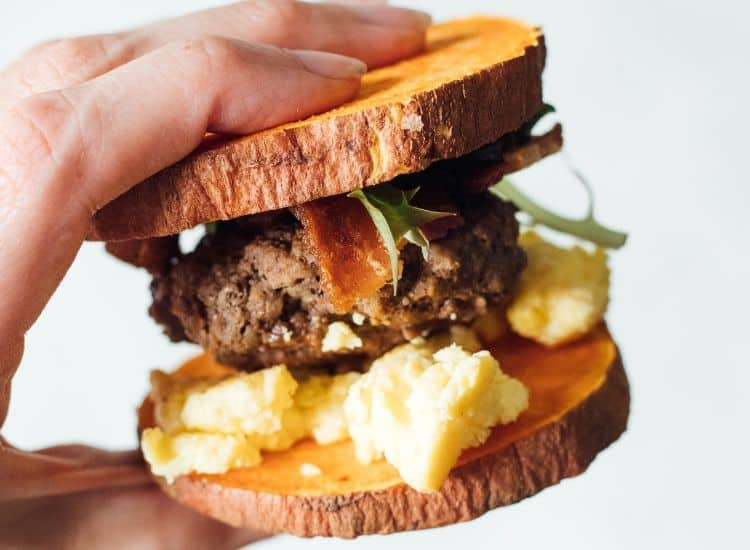 A hand holds a breakfast sandwich including sausage, eggs, bacon, and lettuce on a sweet potato bun.