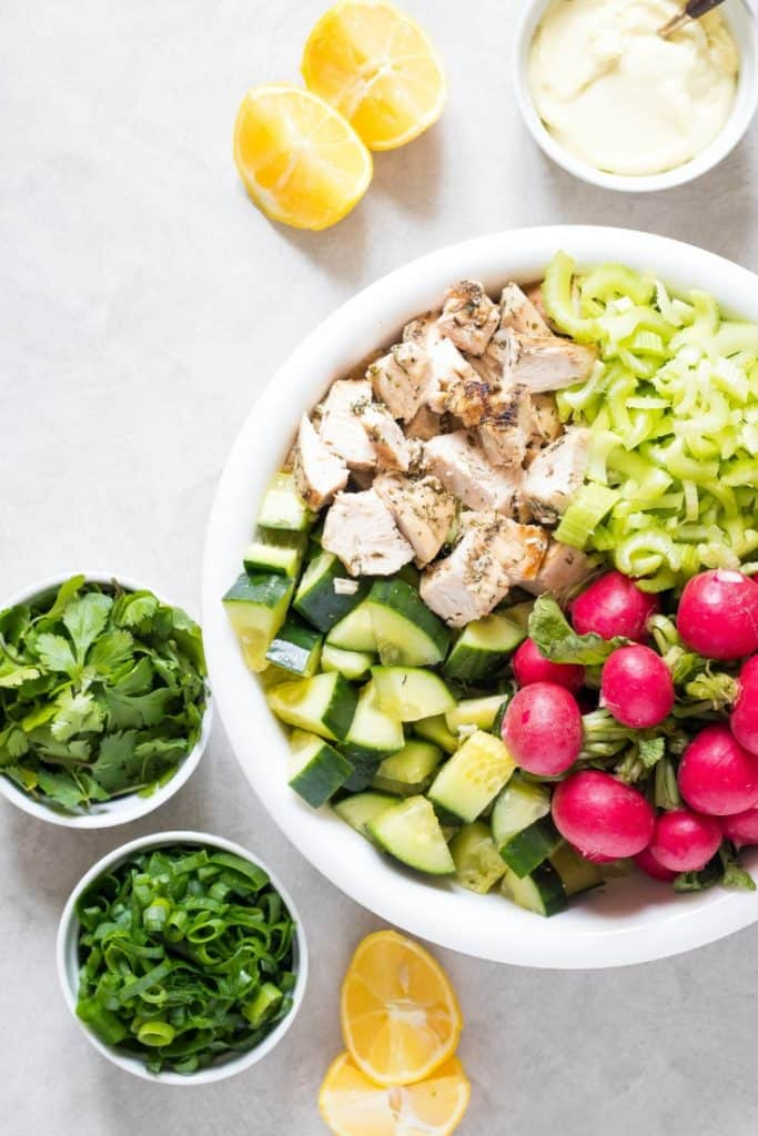 white bowl of whole30 Chicken Salad ingredients like cucumber, radishes, celery, and chicken, with cilantro, green onions, and lemon on the side.