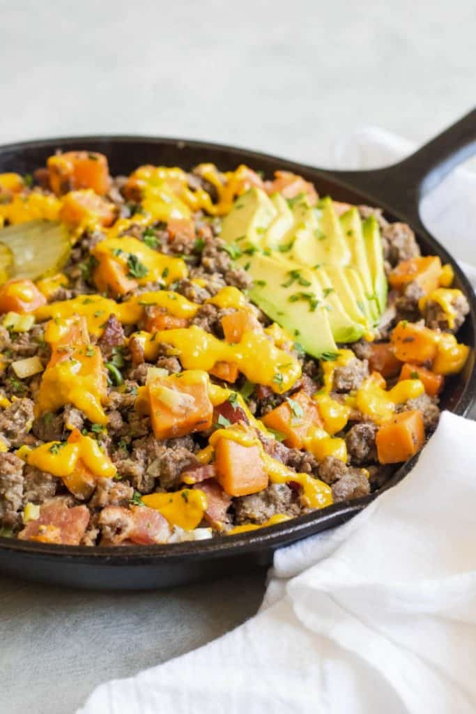 a skillet of ground beef, bacon, dairy free cheese sauce, and avocado sprinkled with cilantro on a grey background comes together to make a delicious Bacon Cheeseburger Casserole
