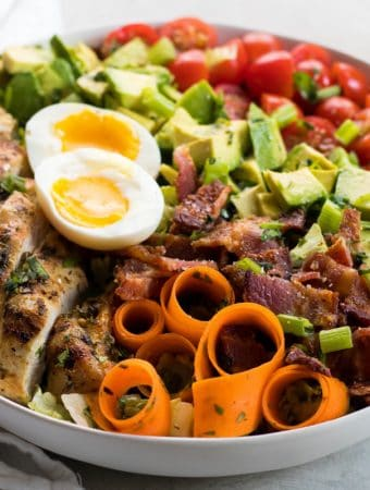 White bowl of keto cobb salad on a grey background with a white linen napkin