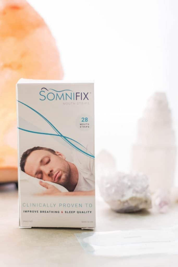 box of Somnifix mouth tape for mouth taping, along with crystals and a salt lamp on a grey background.