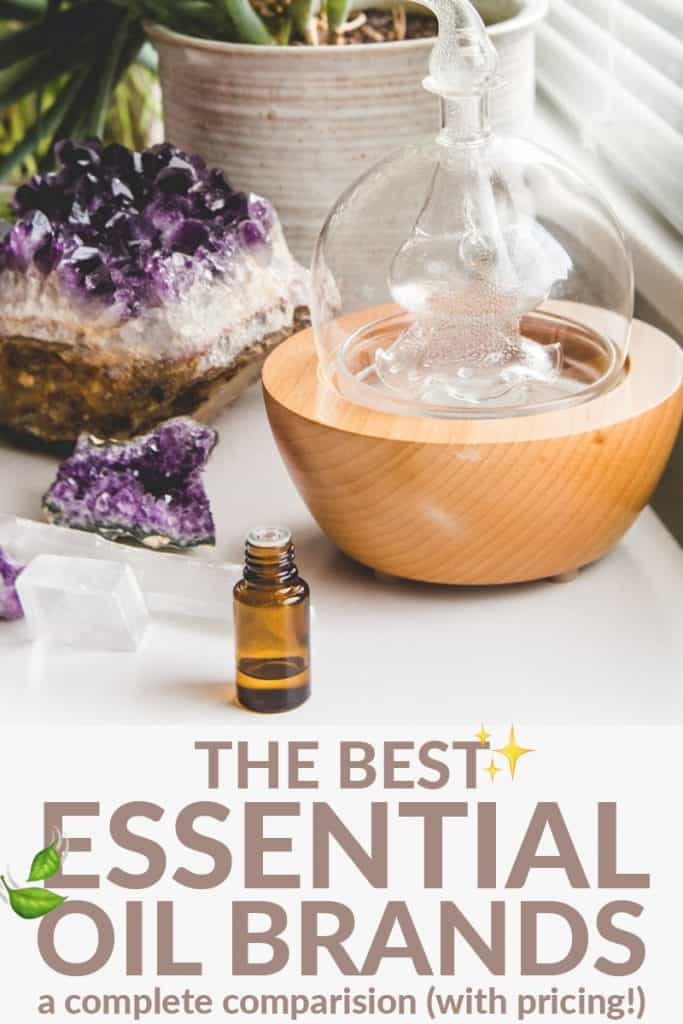"A glass diffuser and essential oil bottle on a white table with a amethyst geode crystal. The words ""best essential oil brands"" are listed below."