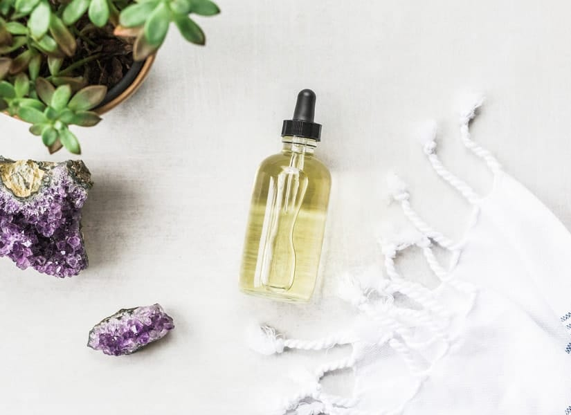 Light gray table with a bottle of face oil for the oil cleansing method, along with an amethyst geode, a turkish towel, and plant.