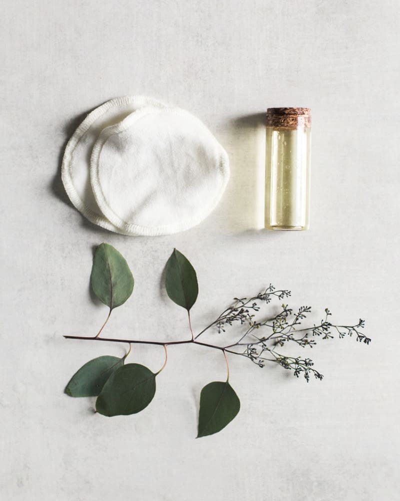 Bottle of face oil for the oil cleansing method on a light gray table with two cotton rounds and flower.