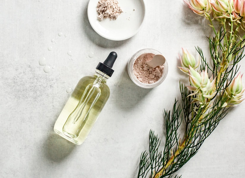 Bottle of face oil for the oil cleansing method on a light gray table with a face mask and flower.