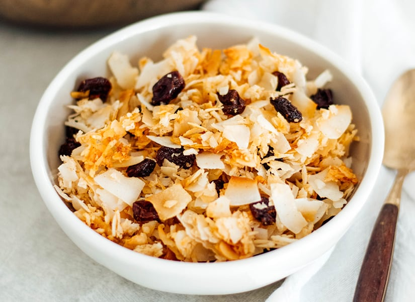 A white bowl full of coconut, nut free, Paleo Granola Cereal with raisins and a gold spoon.