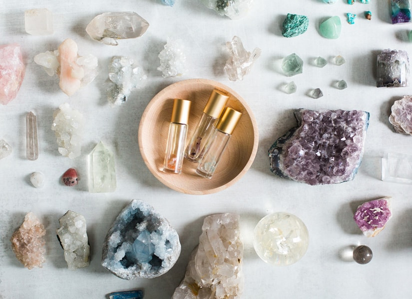A white marble table with crystals and geodes laid out with essential oil roller blends in a wooden bowl in the center of the table.