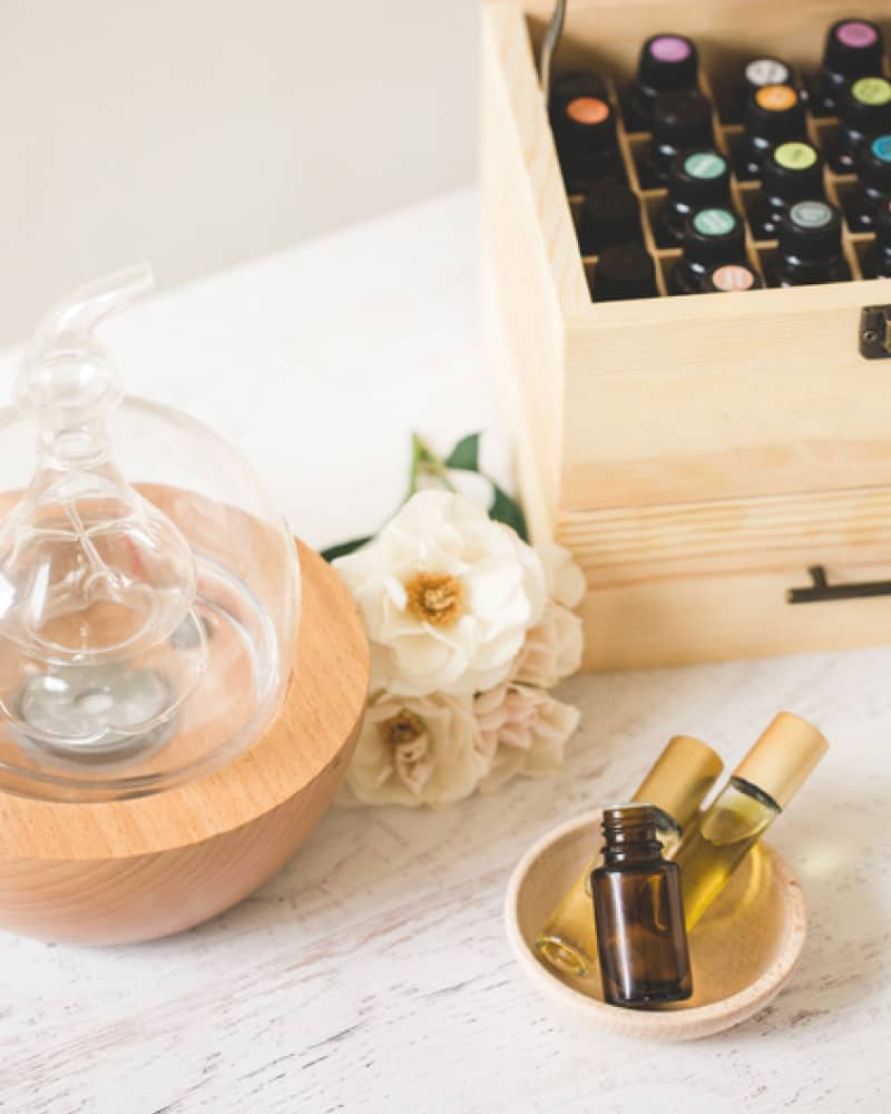 glass and wood diffuser on a white table with a bowl and box of essential oils