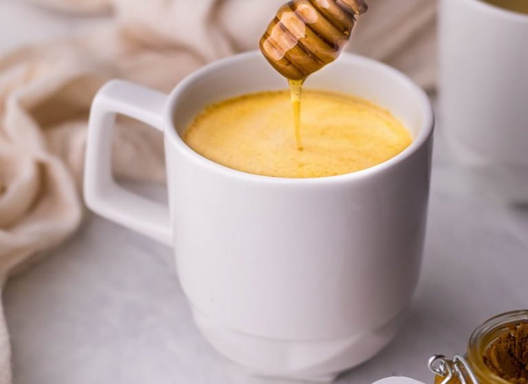 White mug full of turmeric coffee on a white counter with a honey drizzle.