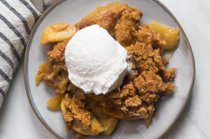 A marble table with a plate of Paleo Apple Crisp and dairy free coconut milk ice cream on top.