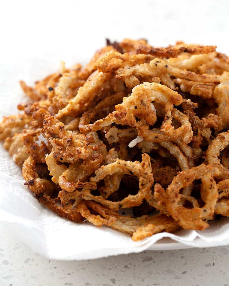 A bowl of gluten free french fried onion rings on a white counter.