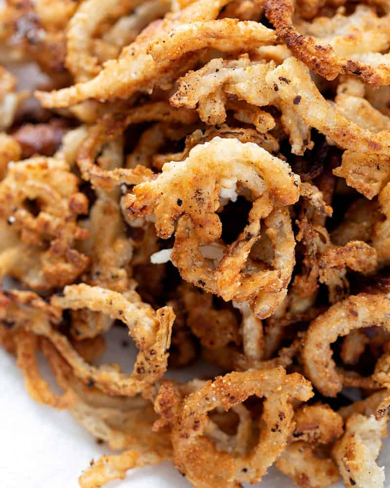 A bowl of gluten free french fried onion rings on a quartz white countertop.