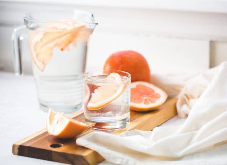 An image of a water jug with grapefruit it in on a marble surface.