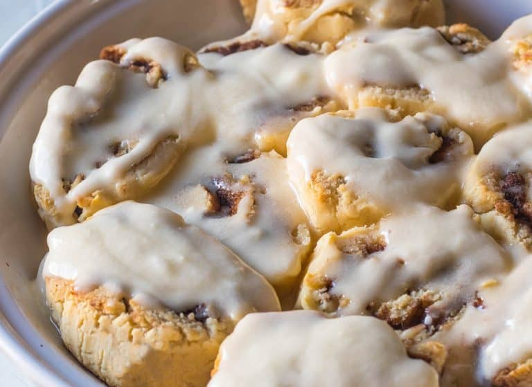 A pie pan of gluten free and paleo cinnamon rolls covered in warm frosting.