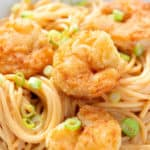 A close up image of a bowl of Bang Bang Fried Shrimp Pasta with green onions as a garnish.