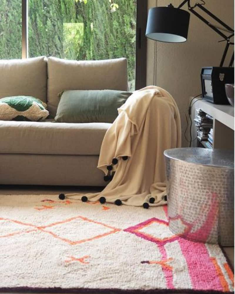 A non toxic rug from Lorena Canal with pink and orange tribal print. The rug is in a living room with a comfortable sofa with pillows and blankets.