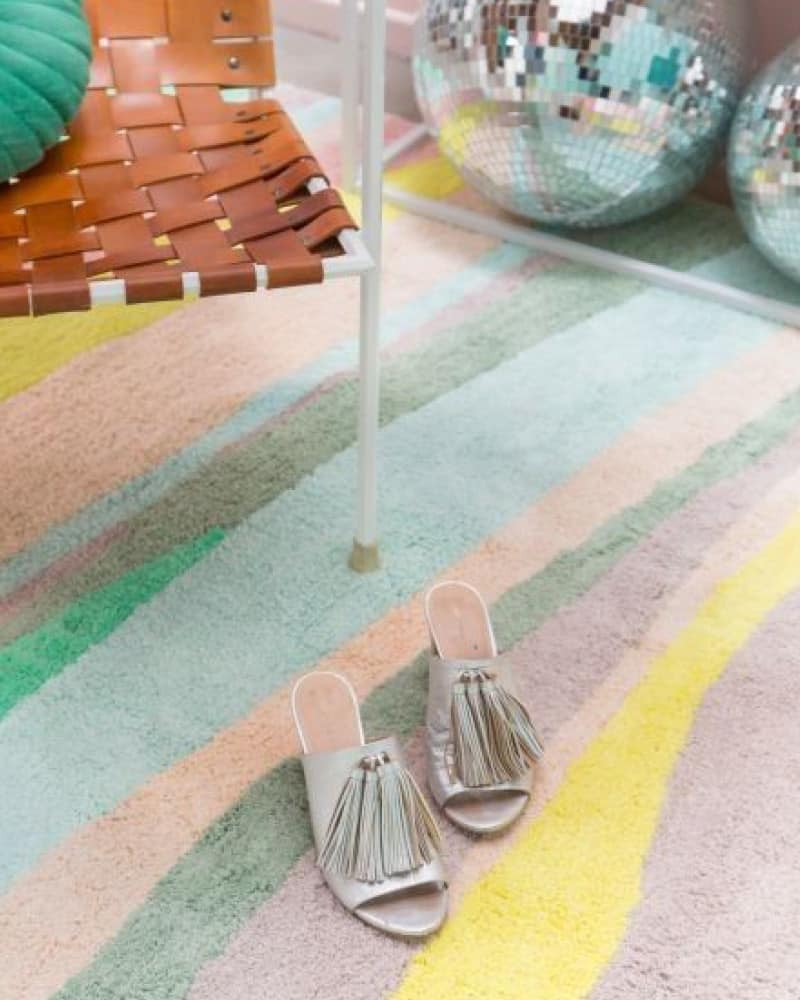 A colorful, playful non toxic rug in light blue, peach, yellow, green and tan in a room with a white chair, tassle shoes, and disco balls.