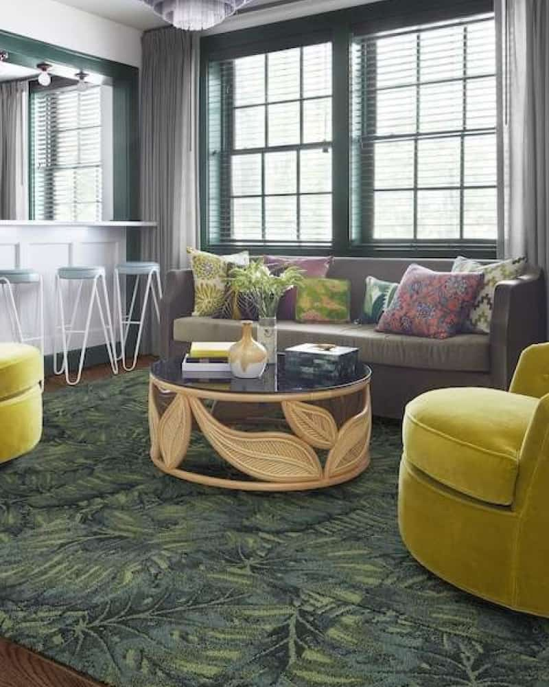 Palm printed non toxic carpet tiles placed together to form a rug in a living room.