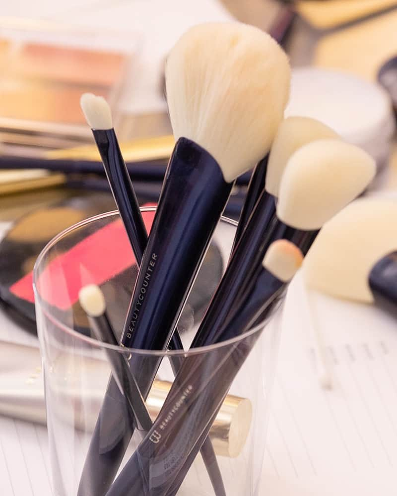 An image of Beautycounter makeup brushes in a glass container.