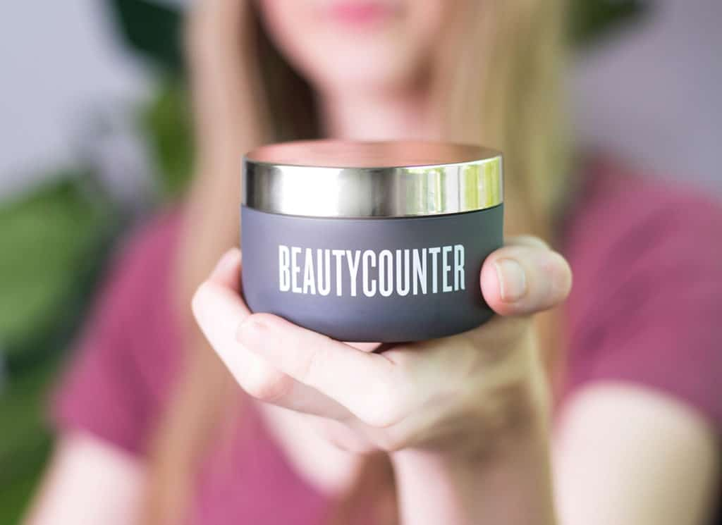 A woman in a pink shirt holds a Beautycounter Cleansing Balm jar.