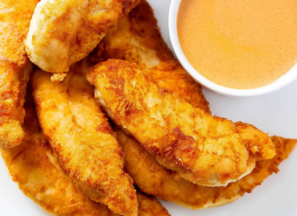 A close up image of whole30 buffalo chicken tenders on a white plate with a ramakin of buffalo dipping sauce.