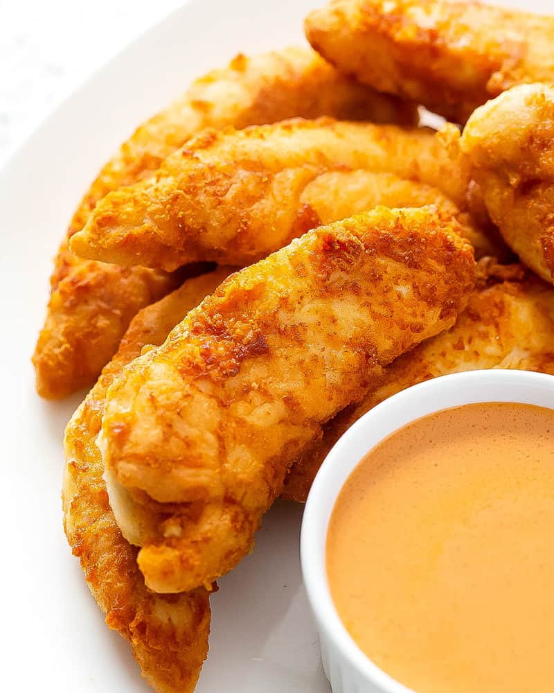 Buffalo chicken tenders on a white plate with a ramakin of buffalo dipping sauce.