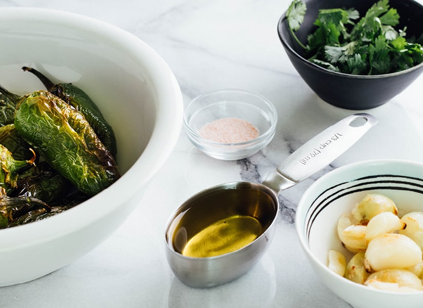 All the ingredients to make Creamy Jalapeno Sauce is spread out on a white marble counter.