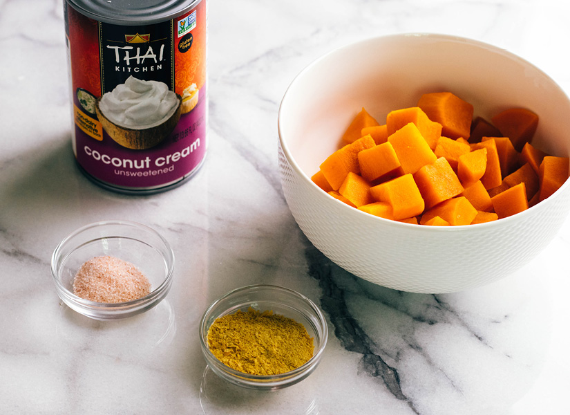 A white marble table with a bowl of steamed and peeled sweet potato, a can of coconut cream, and a small ramekin of sea salt and nutritional yeast flakes.