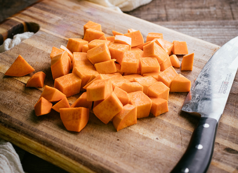 A wooden cutting board on a wood table with cubed and peeled sweet potatoes on it.