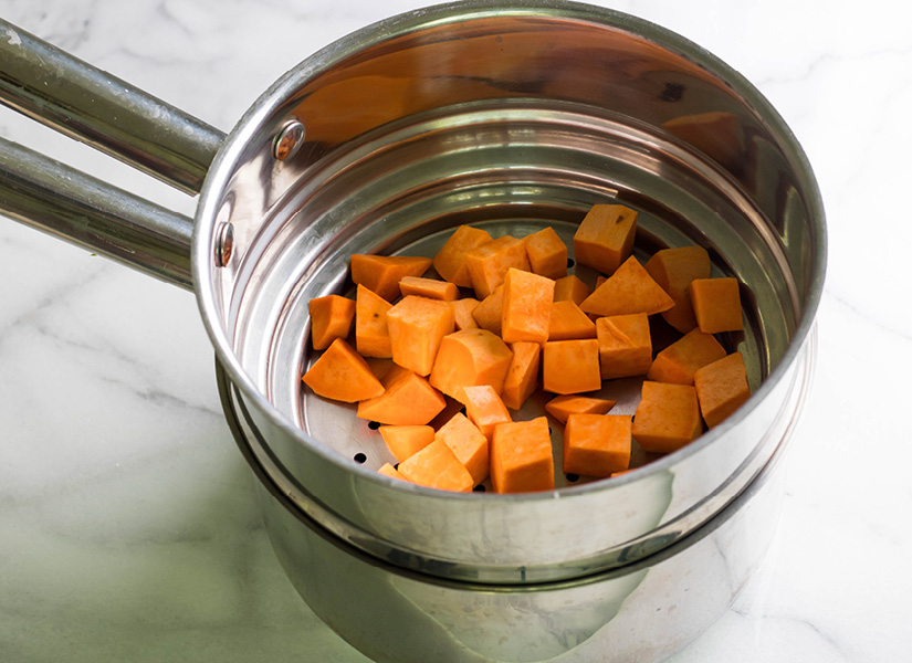 A stainless steel double boiler set with peeled sweet potatoes inside.