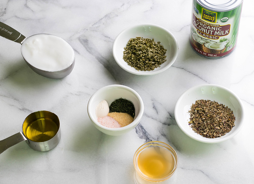 A white marble table has all the ingredients out to make paleo ranch dressing.